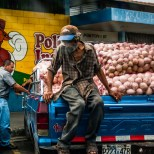 Guy looks over truck full of onions in El Salvador.